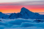 Dent Blanc peak over clouds during a winter sunrise in Swiss Alps. Igloo refuge des Pantalons Blancs, Heremence, Sion, Valais canton, Switzerland, Europe.
