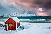 A typical house of fishermen on the snowy Ramberg beach, Lofoten Islands, Norway