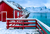 Typical red house reflected in the sea. Reine, Lofoten Islands, Northern Norway