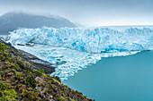 Die nördliche Seite des Perito-Moreno-Gletschers und Eisberge an einem launischen Tag, Departamento Lago Argentino, Provinz Santa Cruz, Argentinien