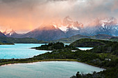 Pehoé Lake with Paine Horns and Cerro Paine covered in mist at dawn. Torres del Paine National Park, Ultima Esperanza province, Magallanes region, Chile.