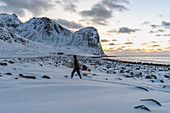 Surfer walking with his surfboard under the arm on Unstad Beach in winter at sunset. Vestvagoy municipality, Nordland county, Northern Norway, Norway.