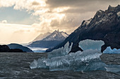 Iceberg floating on Lago Grey with mountains and Grey glacier in the background. Torres del Paine National Park, Ultima Esperanza province, Chile.