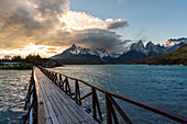 Wooden bridge on Lake Pehoé with Cerro Paine Grande and Paine Horns in the background at sunset. Torres del Paine National Park, Ultima Esperanza province, Chile.