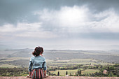 A girl admiring the countryside from Sant'Angelo in Colle, Siena, Tuscany, Italy, Europe