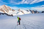 Alpinist over the Mont Blanc glacier watching Aiguille du Midi, near Punta Helbronner (3462m), Mont Blanc, Courmayeur, Aosta, Aosta Valley, Italy
