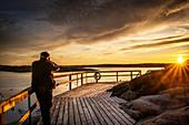 A man watches the sunset on a jetty in the archipelago, Ellös, Orust, Bohuslän, Sweden