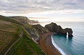 Aerial view at sunrise of the Durdle Door, a natural limestone arch on the Jurassic Coast near Lulworth in Dorset, Southern England.