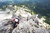 A climber along the via ferrata Olivieri on the Tofana di Mezzo with the Dolomiti Bellunesi National Park in the background, Belluno province, Veneto Italy