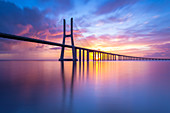 A colorful sunrise behind the Vasco da Gama bridge, reflected on the Tagus River. Lisbon, Portugal, Europe.