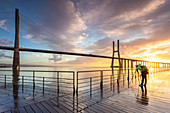 A photographer taking pictures on a pier during a colorful sunrise in front of the Vasco da Gama bridge. Lisbon, Portugal, Europe.