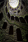 View from below of the spiral stairs inside the inverted tower, called also initiation well, at Quinta da Regaleira Palace, Sintra, Portugal, Europe.