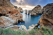 Cloudy sunrise at the yellow and red cliffs of Ponta da Piedade. Lagos, Algarve, Portugal, Europe.