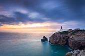 The cliffs and lighthouse of Cabo De San Vicente at sunset, overlooking the Atlantic Ocean. Sagres, Vila do Bispo, Algarve, Portugal, Europe.