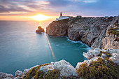 The cliffs and lighthouse of Cabo De San Vicente at sunset, overlooking the Atlantic Ocean. Sagres, Vila do Bispo, Algarve, Portugal, Europe.