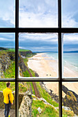 View of a tourist admiring the Downhill beach from inside the Mussenden temple. Castlerock, County Antrim, Ulster region, Northern Ireland, United Kingdom.