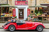 United Kingdom, Worcestershire, Cotswold district, Cotswolds region, Broadway Deli deli front of a convertible car with the British automaker Morgan