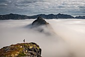HIKER AT THE SUMMIT OF MOUNT HESTEN CONTEMPLATING THE PEAKS EMERGING FROM A SEA OF CLOUDS, FJORDGARD, SENJA, NORWAY