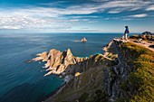 HIKER AT THE SUMMIT OF MOUNT MATIND ABOVE THE CRAGGY COAST OF THE ISLAND OF ANDOYA, NORWAY