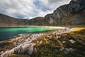 HIKER APPROACHING THE BEACH OF HOYVIKA, WHITE SAND AND TURQUOISE WATER SURROUNDED BY MOUNTAINS, STAVE, ANDOYA, NORWAY