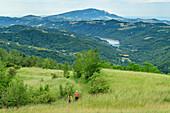 Man and woman hiking through meadow, Grande Anello dei Sibillini, Sibillini Mountains, Monti Sibillini, Monti Sibillini National Park, Parco nazionale dei Monti Sibillini, Apennines, Marche, Umbria, Italy