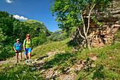 Man and woman hiking past rock face, Grande Anello dei Sibillini, Sibillini Mountains, Monti Sibillini, National Park Monti Sibillini, Parco nazionale dei Monti Sibillini, Apennines, Marche, Umbria, Italy