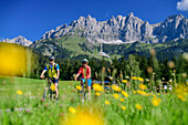 Man and woman cycling with Kaiser Mountains in the background, Kaiser Mountains, Tyrol, Austria