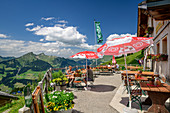 Guests sit on the sun terrace of the Alpe Oberpartnun, Bregenzerwald Mountains in the background, Großes Walsertal Biosphere Reserve, Lechquellen Mountains, Vorarlberg, Austria