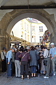 Group of tourists under an archway in downtown Bratislava, Slovakia.