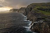 Steep coast in the west of the island of Vágar with the waterfall Bøsdalafossur and the rock needle Geitaskoradrangur near the largest lake in the Faroe Islands, Leitisvatn, Faroe Islands