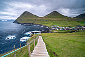 View from the steep coast to the sea. A wooden staircase facilitates the ascent on the steep slope above Gjógv, Faroe Islands.