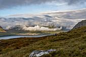 Blick vom Klakkur auf das Dorf Leirvík mit sonnendurchschienen Wolken und der typischen Graslandschaft, Färöer Inseln