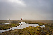 Hiker stands on a mirror-smooth water surface in the high moor of the Klakkur, Klaksvík, Faroe Islands.