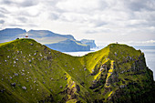Lighthouse Kallur and tourists at the northern tip of the island Kalsoy, Faroe Islands