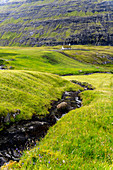 Church with a grassy roof and creek in the foreground, in one of the most beautiful places in the world, Saksun, Streymoy Island in the Faroe Islands.