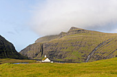 View of the church of Saksun, with a grassy roof in front of the lagoon, Streymoy Island in the Faroe Islands.