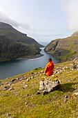 Frau blickt auf die Lagune von Saksun, Insel Streymoy auf den Färoer Inseln