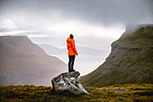 Hiker enjoys the view of the beautiful landscape of the Faroe Islands.