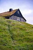 Blick auf die historisches Haus von Saksun, mit grasbewachsenem Dach, Insel Streymoy auf den Färöer Inseln