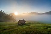 Die kleinen Hütten über dem nebelverhangenen Geroldsee an einem Frühherbstmorgen, Krün, Bayern, Deutschland