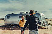 Couple running towards each other in front of Airstream in Flagstaff, Grand Canyon, Arizona, USA, North America