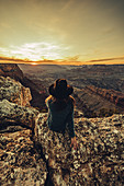 Woman looks out over Grand Canyon at sunset, Grand Canyon National Park, Arizona, USA, North America