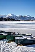 Boats on the shore of frozen Hopfensee in winter, Hopfen am See, Füssen, Ostallgäu, Bavaria, Germany