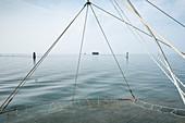 Blick auf ein Stelzenhaus, im Vordergrund ein Fischernetz, Hafen von Pellestrina, Lagune von Venedig, Venetien, Italien, Europa