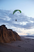 Paraglider pilots at sunset on Point Reyes Beach, California, USA.