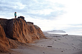 Small child in the evening light on the cliff at Point Reyes Beach, California, USA.