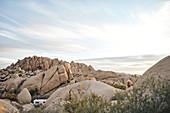 Felsformation mit kleinem Kind und Camper im Joshua Tree Park, Kalifornien, USA