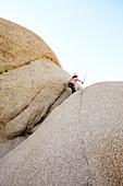 Boy playing on a rock of Jumbo Rocks in Joshua Tree Park, California, USA.