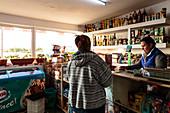 Village shop in the Danube Delta, customer and saleswoman, Mila 23, Tulcea, Romania.