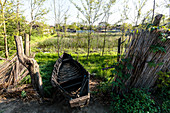 A derelict fishing boat lies in the garden next to the reed fence in the Danube Delta in April, Mila 23, Tulcea, Romania.